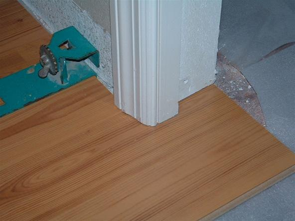 under-cutting-door-jambs-with-hand-saw-before-installing-laminate-flooring.w654.jpg